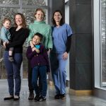 Mothers Megan Mueller, Assistant Professor of Clinical Sciences, with her son Oliver, 2, Marieke Rosenbaum, Research Assistant Professor of Infectious Disease and Global Health, with her son Zee, 7, and Annie Wayne, Assistant Professor of Clinical Sciences, pose for a group photo in the Agnes Varis Campus Center at Cummings School of Veterinary Medicine