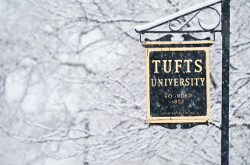 Tufts University sign hanging on a post on campus in the snow