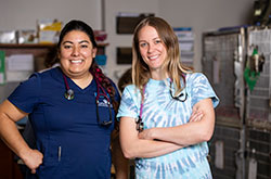Veterinarians Kayla Sample and Jane Waterfall, V18 posing for camera at Tufts at Tech community medicine clinic