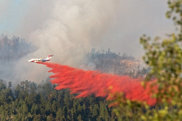 Fire retardants being sprayed from a jet over wildfires in California