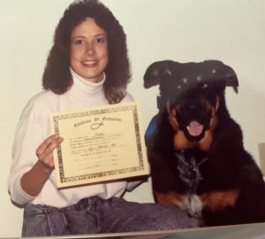Bloniasz poses with Buddy, a Rottweiler-German shepherd she adopted as a puppy and a certificate recognizing the completion of his obedience training.