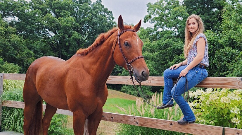 Rachell Perkins sitting on a fence with her horse, Travis, who is an Appaloosa, next to her.